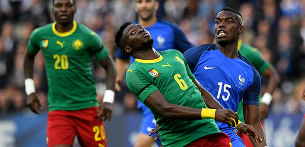 France's midfielder Paul Pogba (R) vies for the ball with Cameroon's defender Ambroise Oyongo Bitolo during the friendly football match between France and Cameroon, at the Beaujoire Stadium in Nantes, western France, on May 30, 2016. / AFP PHOTO / FRANCK FIFE